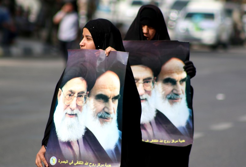 Iraqi Shiite Muslim women hold posters bearing portraits of Iran's supreme leader Ayatollah Ali Khamenei (L) and Iran's founder of the Islamic Republic, Ayatollah Ruhollah Khomeini (R) during a parade marking Al-Quds (Jerusalem) International Day organised by the Popular Mobilisation units in the southern Iraqi city of Basra on July 10, 2015. AFP PHOTO / HAIDAR MOHAMEED ALI        (Photo credit should read HAIDAR MOHAMMED ALI/AFP/Getty Images)