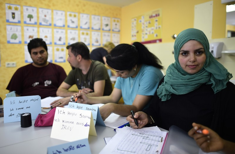 Refugees attend a German course in a classroom at a temporary home providing assistance for refugees in Berlin's Gatow district on August 6, 2015. Germany, overwhelmed by people fleeing war and poverty, is trying to deter asylum seekers from the Balkans, a region considered safe at least from armed conflict. AFP PHOTO / TOBIAS SCHWARZ        (Photo credit should read TOBIAS SCHWARZ/AFP/Getty Images)