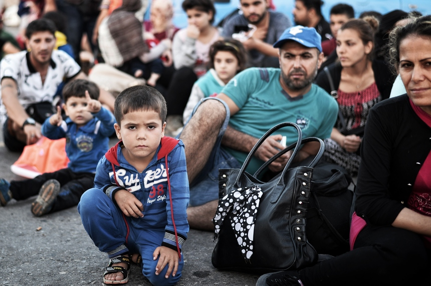 Newly arrived Syrian migrants wait in the port of Kos to be registered on the Eleftherios Venizelos liner on August 17, 2015. Authorities on the island of Kos have been so overwhelmed that the government sent a ferry to serve as a temporary centre to issue travel documents to Syrian refugees -- among some 7,000 migrants stranded on the island of about 30,000 people. The early hours are the safest time for migrants travelling from Turkey to the Greek islands just across the water, which have seen a huge influx of refugees escaping the civil war in Syria and chaos in Afghanistan since the beginning of this year. AFP PHOTO /LOUISA GOULIAMAKI        (Photo credit should read LOUISA GOULIAMAKI/AFP/Getty Images)
