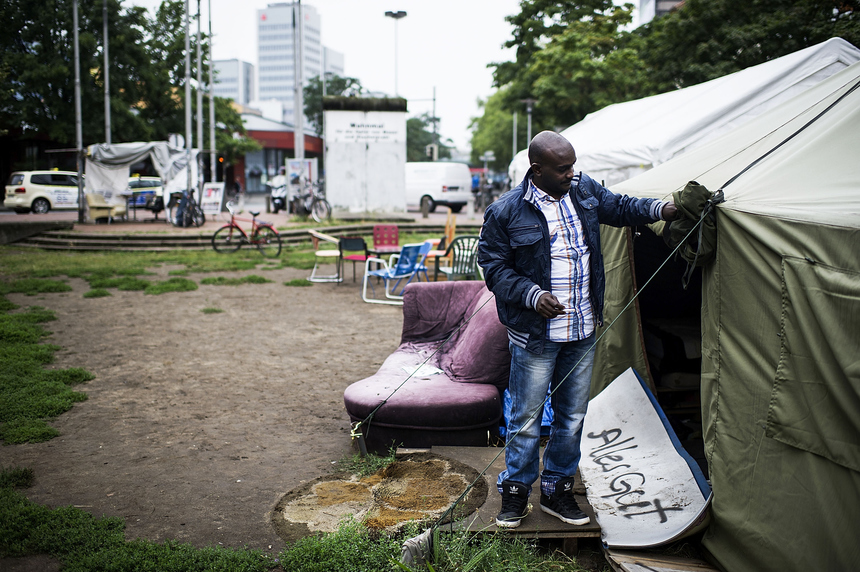 HANOVER, GERMANY - AUGUST 17:  A Sudanese refugee walks through a refugee camp at Weissekreuzplatz on August 17, 2015 in Hanover, Germany. In May 2014, refugees mainly from the Sudan set up the makeshift camp to protest and draw attention to the political and ethical situation of their home country and to seek asylum in Germany. City authorities have tolerated the camp located in the city center, but talks to end the camp are currently on hold. Germany and other European countries are currently struggling to deal with a record number of migrants, many of them from Syria and North-Africa, crossing the Mediterranean Sea or through Greece and Hungary further into North Europe.  (Photo by Alexander Koerner/Getty Images)