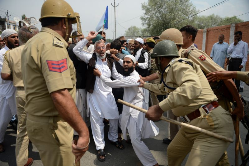 Indian police try to detain supporters of the hardline faction of the All Parties Hurriyat Confrence (APHC) as they clash during a protest following the house arrest of APHC leader, Syed Ali Shah Geelani in Srinagar on August 23, 2015.  Geelani was placed under house arrest shortly before attempting to leave his residence to address a seminar organised by the APHC.  Police used tear smoke shells and water cannons to disperse hundreds of supporters protesting Geelani's arrest.  AFP PHOTO/ Tauseef MUSTAFA        (Photo credit should read TAUSEEF MUSTAFA/AFP/Getty Images)