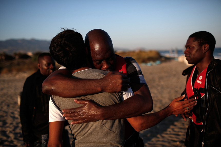 KOS, GREECE - AUGUST 29:  A migrant from Gambia embraces a friend after safely completing a journey across a three mile stretch of the Aegean Sea in a small boat from Turkey August 29, 2015 in Kos, Greece. Migrants from many parts of the Middle East and African nations continue to flood into Europe before heading from Athens, north to the Macedonian border. Since the beginning of 2015 the number of migrants using the so-called 'Balkans route' has exploded with migrants arriving in Greece from Turkey and then travelling on through Macedonia and Serbia before entering the EU via Hungary. The number of people leaving their homes in war torn countries such as Syria, marks the largest migration of people since World War II.  (Photo by Win McNamee/Getty Images)