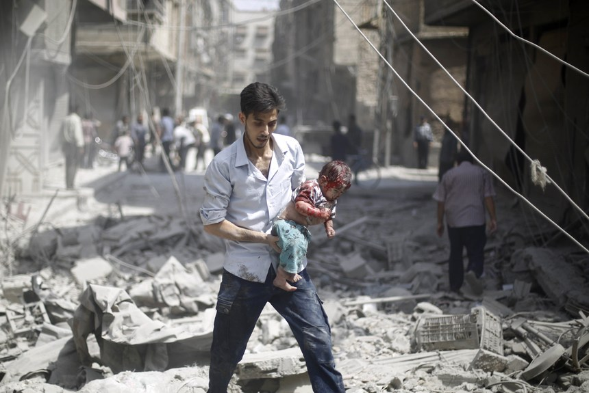 GRAPHIC CONTENT A Syrian man carries a wounded baby following a reported air strike by Syrian government forces in the rebel-held area of Douma, east of the capital Damascus, on August 30, 2015. More than 240,000 people have been killed since Syria's conflict began in March 2011, and half of the country's population has been displaced by the war. AFP PHOTO / SAMEER AL-DOUMY        (Photo credit should read SAMEER AL-DOUMY/AFP/Getty Images)
