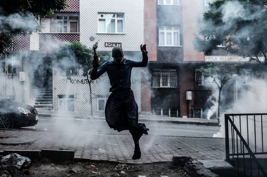 A masked Kurdish militant holds a molotov cocktail while jumping away from tear gas canisters during clashes with Turkish police on August 30,2015 in the Gazi district of Istanbul. Three policemen, a 12-year-old boy and three Kurdish rebels died Sunday in continuing violence in Turkey's restive Kurdish-dominated southeast, a local security source said. AFP PHOTO / OZAN KOSE        (Photo credit should read OZAN KOSE/AFP/Getty Images)