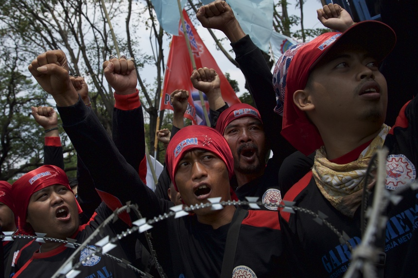 JAKARTA, INDONESIA - SEPTEMBER 01:  Indonesian workers and labor activists shout slogans in front of the Presidential Palace to protest against higher prices for basic goods and increasing layoffs for factory workers on September 1, 2015 in Jakarta, Indonesia.  Indonesia's currency, the Rupiah has weakened against the dollar making imported goods, many of which are necessities, more expensive at the same time a global trade slump has forced the closing of many export based businesses. (Photo by Ed Wray/Getty Images)