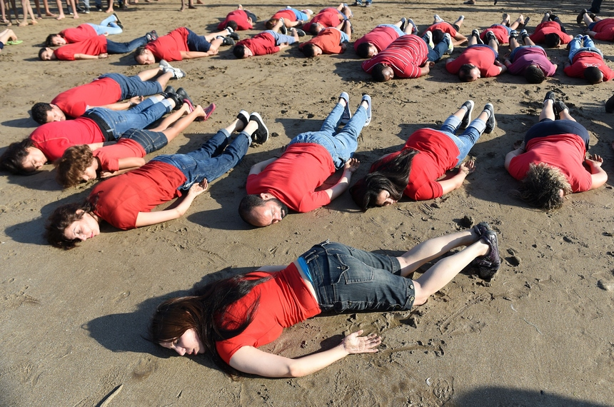 Moroccans adopt the position of the lifeless body of Syrian three-year-old Aylan Kurdi, who drowned while fleeing the Syrian war, during a rally to pay tribute to the tiny boy on September 7, 2015 on a beach in the  capital Rabat. Aylan's body was photographed lying face down in the sand with red and blue clothing on a Turkish beach, in a bleak image that rapidly went viral on social media.    AFP PHOTO / FADEL SENNA        (Photo credit should read FADEL SENNA/AFP/Getty Images)