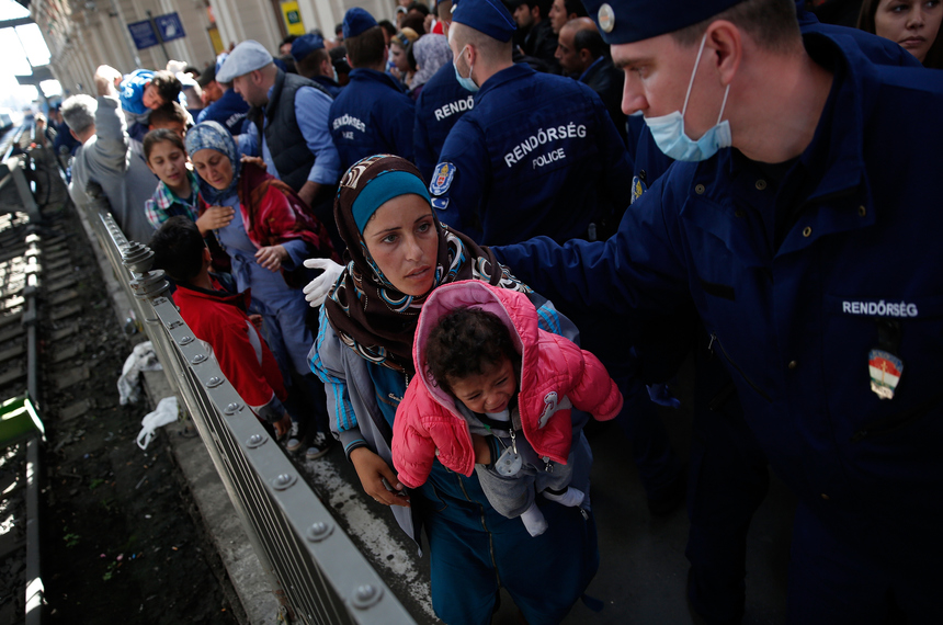 BUDAPEST, HUNGARY - SEPTEMBER 09:  A Syrian woman carries her baby on her chest as she leads family members past Hungarian police after being caught in a surge of migrants attempting to board a train bound for Munich, Germany at the Keleti railway station on September 9, 2015 in Budapest, Hungary. Migrants in Budapest are concerned that governments will soon close or severely limit continued travel access to Austria and Germany. Since the beginning of 2015 the number of migrants using the so-called 'Balkans route' has exploded with migrants arriving in Greece from Turkey and then travelling on through Macedonia and Serbia before entering the EU via Hungary. The number of people leaving their homes in war torn countries such as Syria, marks the largest migration of people since World War II.  (Photo by Win McNamee/Getty Images)