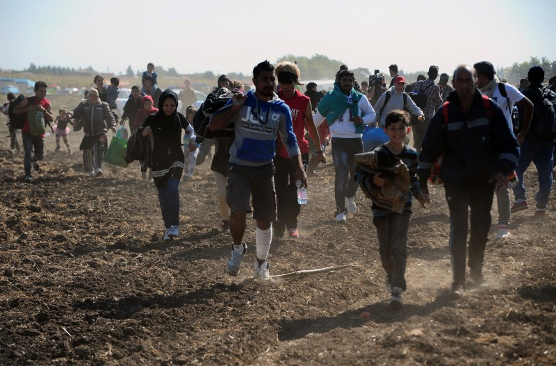 Migrants run over a field as their crowd broke out of at collection point near Roszke village at the Hungarian-Serbian border on September 9, 2015. Some 400-500 migrants on Wednesday broke through police lines in Hungary near the main crossing point from Serbia.  AFP PHOTO / CSABA SEGESVARI        (Photo credit should read CSABA SEGESVARI/AFP/Getty Images)