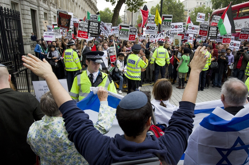 Police stand between pro-Israeli (foreground) and pro-Palestinian demonstrators outside the gates of Downing Street in London on September 9, 2015. Over 100 pro-Israeli demonstrators and hundreds of pro-Palestinian activists rallied in front of Downing Street in London ahead of a planned visit of Israeli Prime Minister Benjamin Netanyahu. Netanyahu visits Britain this week for talks with his counterpart David Cameron as the right-wing Israeli leader faces diplomatic pressure over West Bank settlements and stalled peace efforts. AFP PHOTO / JUSTIN TALLIS        (Photo credit should read JUSTIN TALLIS/AFP/Getty Images)