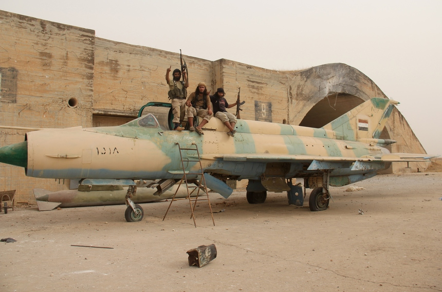 Members of Al-Qaeda's Syrian affiliate and its allies sit on top of a former Syrian army MiG-21 figther jet after they seized the Abu Duhur military airport, the last regime-held military base in northwestern Idlib province on September 9, 2015 in the latest setback for President Bashar al-Assad's forces. Al-Nusra Front and a coalition of mostly Islamist groups captured the military airport after a siege that lasted two years, the Syrian Observatory for Human Rights monitor said. AFP PHOTO / OMAR HAJ KADOUR        (Photo credit should read OMAR HAJ KADOUR/AFP/Getty Images)