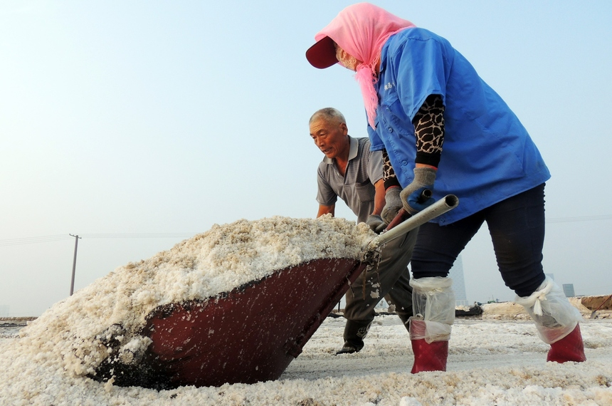 """Chinese workers collect crude salt at Taibei Saltern in Lianyungang, east China's Jiangsu Province on September 10, 2015. China's factory gate prices fell at their fastest rate in six years in August, the government said on September 10, as Premier Li Keqiang warned that transforming the world's second-largest economy will be a """"painful and treacherous"""" process.   AFP PHOTO  -- CHINA OUT        (Photo credit should read STR/AFP/Getty Images)"""