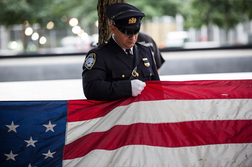 NEW YORK, NY - SEPTEMBER 11:  A Port Authority Police officer prepares to present an American flag that survived the terrorist attacks of September 11, 2001, during an anniversary ceremony on September 11, 2015 in New York City. Today marks the 14th anniversary of the attacks where nearly 3,000 people were killed in New York, Washington D.C. and Pennsylvania.  (Photo by Andrew Burton/Getty Images)