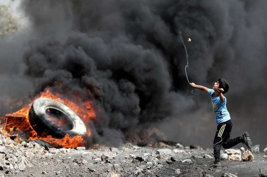 A Palestinian boy uses a slingshot to throw stones towards Israeli army troops during clashes in the West Bank village of Kfar Qaddum, on September 11, 2015.  AFP PHOTO / THOMAS COEX        (Photo credit should read THOMAS COEX/AFP/Getty Images)
