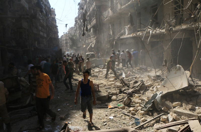 Syrians check the rubble following an air strike by government forces on the eastern Shaar neighbourhood of the northern Syrian city of Aleppo on September 17, 2015. Once Syria's economic powerhouse, Aleppo has been ravaged by fighting since the rebels seized the east of the city in 2012, confining government forces to the west. AFP PHOTO / FADI AL-HALABI        (Photo credit should read Fadi al-Halabi/AFP/Getty Images)