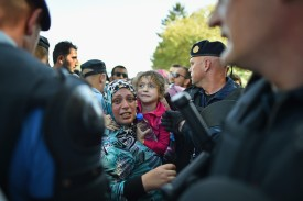 TOVARNIK, CROATIA - SEPTEMBER 17:  A woman and a young child look on as migrants force their way through police lines at Tovarnik station to board a train bound for Zagreb on September 17, 2015 in Tovarnik, Croatia. Migrants are now diverting to Croatia from Serbia after Hungary closed its border with Serbia, with the majority of them trying to reach Germany amid divisions within the European Union over how to manage the ongoing crisis. (Photo by Jeff J Mitchell/Getty Images)