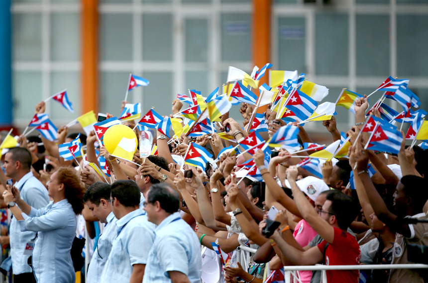 HAVANA, CUBA - SEPTEMBER 19:  Youngsters wave Cuban and Vatican flags during the arrival of Pope Francis at Jose Marti International Airport on September 19, 2015 in Havana, Cuba. Pope Francis is at the beginning of a three day visit to Cuba where he will meet President Raul Castro and hold Mass in Revolution Square before travelling to Holguin, Santiago de Cuba and El Cobre then onwards to the United States.  (Photo by Carl Court/Getty Images)