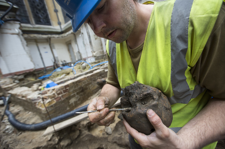 LONDON, ENGLAND - SEPTEMBER 21:   (EDITORS NOTE:  IMAGES STRICTLY EMBARGOED FROM ALL USAGE UNTIL 00:01 BST ON WEDNESDAY SEPTEMBER 23, 2015)   Archaeologist Paw Jorgensen works on a skull that forms part of a collection of bones that were found among the stepped footings of Westminster Abbey's south transept, on September 21, 2015 in London, England. The footings were built from Reigate stone between 1246 and1250, during the reign of Henry III, and back filled with charnel material comprising mostly of femurs and skulls from earlier burials. The square hole on the skull is likely from pick axes used to dig out the bones in the 13th century. The area is currently being excavated as part of the transform of part of the 13th-century Triforium into a new viewing and gallery area that will be open to the public for the first time. As well as exhibiting many historical objects from the abbey, the new £19m GBP space will give visitors views down over the abbey buildings and the neighbouring Palace of Westminster. The work is due to be completed by 2018  (Photo by Dan Kitwood/Getty Images)