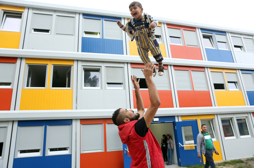 BERLIN, GERMANY - SEPTEMBER 23:  A Kurdish Syrian migrant plays with 3-year-old Kurish Syrian child refugee, Ivan, at a temporary shelter for migrants constructed from shipping containers, on September 23, 2015 in the Koepenick district of Berlin, Germany. Almost half a million refugees, a number expected to increase, have crossed into Europe so far this year. After weeks of deliberations, the European Union decided upon a quota plan the previous day to distribute a share of them amongst EU member states in the largest instance of mass migrant movement on the Continent since World War II. Integration poses a particular challenge in Germany, where an earlier example of large-scale immigration by Gastarbeiters, or 'guest workers' brought over in a booming post-war economy, has been criticized for its failures in terms of incorporating foreigners, particularly Turks, into society.  (Photo by Adam Berry/Getty Images)