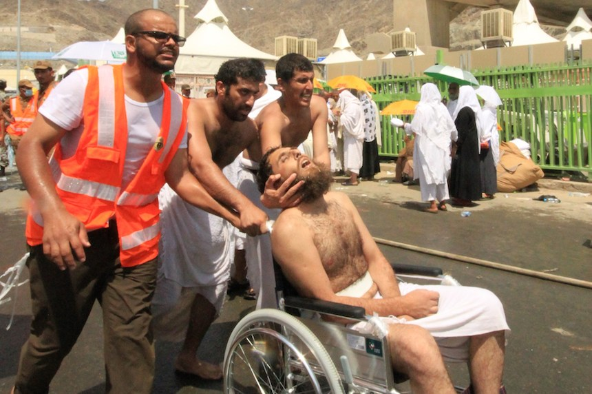 Saudi emergency personnel and Hajj pilgrims push a wounded person in a wheelchair at the site where at least 450 were killed and hundreds wounded in a stampede in Mina, near the holy city of Mecca, at the annual hajj in Saudi Arabia on September 24, 2015. The stampede, the second deadly accident to strike the pilgrims this year, broke out during the symbolic stoning of the devil ritual, the Saudi civil defence service said. AFP PHOTO / STR