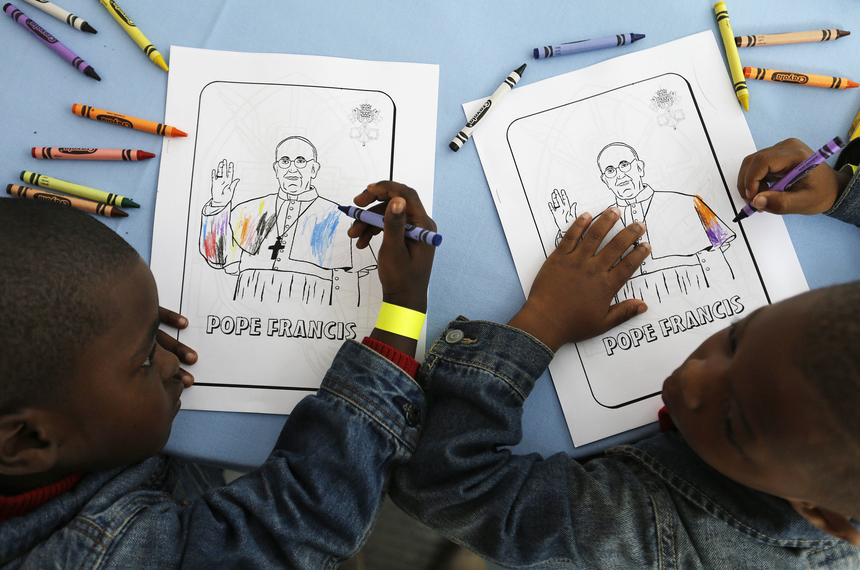 WASHINGTON, DC - SEPTEMBER 24:  Kaydn Dorsey, 4, left, and Lionel Perkins, 4, draw on a coloring sheet bearing the image of Pope Francis as they wait for him to arrive on a visit to Catholic Charities of the Archdiocese of Washington September 24, 2015, in Washington, DC. The charity serves dinner to about 300 homeless people daily at the site, and it will serve a meal during the pope's visit. (Photo by David Goldman-Pool/Getty Images)