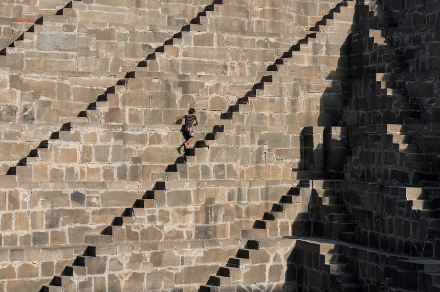 An Indian boys walks up the steps of the historic Chand Baori stepwell in Abhaneri village in Rajasthan on September 24, 2015. For a few hours on one day each year local residents are permitted to descend into the 100-foot-deep, 1,200-year-old stepwell, as Hindu devotees in the area mark a local festival, at the same time as Hindus worldwide observe Ganesh Chaturthi festivities. Chand Baori is one of the oldest and largest stepwells in the world, with some 3,500 steps laid out in a geometric design down to the water at its base. AFP PHOTO / ALEX OGLE        (Photo credit should read Alex Ogle/AFP/Getty Images)
