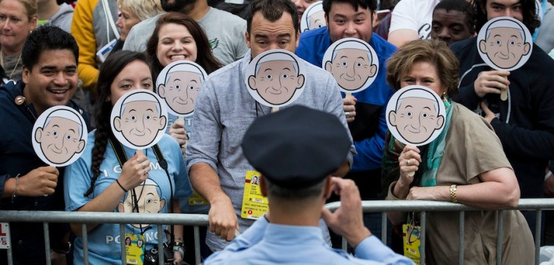 """PHILADELPHIA, PA - SEPTEMBER 26: A police officer takes a photo of a group holding """"Pope Emoji"""" smasks while they wait for Pope Francis to arrive at Cathedral Basilica of Saints Peter and Paul on September 26, 2015 in Philadelphia, Pennsylvania. After visiting Washington and New York City, Pope Francis concludes his tour of the U.S. with events in Philadelphia on Saturday and Sunday. (Drew Angerer/Getty Images)"""
