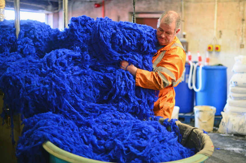 LEWIS, SCOTLAND - MAY 13:  Callum Macleod dying wool at the Harris Tweed Hebrides Company in Shawbost on May 13, 2014 in Stornoway, Scotland. Sales in one of Scotlands last cottage industries are soaring with Japan, Russia and Germany being some of the largest international importers of the cloth.   (Photo by Jeff J Mitchell/Getty Images)