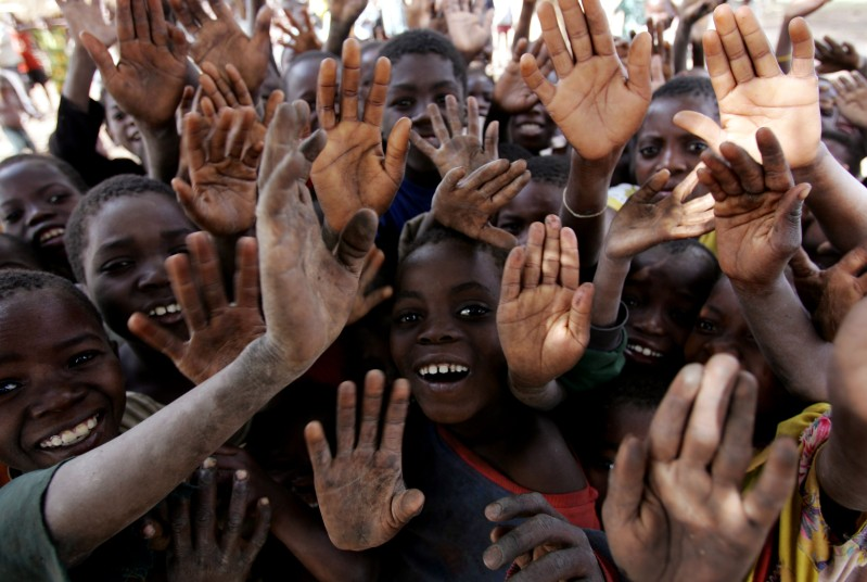 MOZAMBIQUE - JUNE 30:  Children wave to the media as they gather together June 30, 2005 in Mozambique. Since Mozambique's 15-year civil war ended in 1992, the country has made a strong recovery, but it has suffered setbacks such as severe floods in 2000 and 2001, followed by two years of drought in 2002 and 2003. These disasters have had a huge impact and led to widespread food shortages and an increase in outbreaks of infectious diseases such as cholera, measles and meningitis. About 13 percent of babies die before their first birthday, 20 percent of children die before the age of five and 48 percent of the country's children are chronically malnourished. The HIV/AIDS pandemic is having a devastating effect on families, many of whom suffer from poverty and a lack of basic services, with tens of thousands of children orphaned, many of them also HIV positive or already ill with AIDS.  (Photo by Graeme Robertson/Getty Images)
