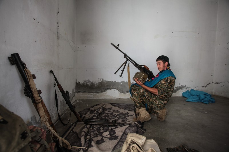 TAL ABYAD, SYRIA - JUNE 19: (TURKEY OUT) A Kurdish People's Protection Units, or YPG fighter controls the weapons in downtown of Tal Abyad, Syria. June 19, 2015. Kurdish fighters with the YPG took full control of Tal Abyad, dealing a major blow to the Islamic State group's ability to wage war in Syria. Mopping up operations have started to make the town safe for the return of residents from Turkey, after more than a year of Islamic State militants holding control of the town. (Photo by Ahmet Sik/Getty Images)