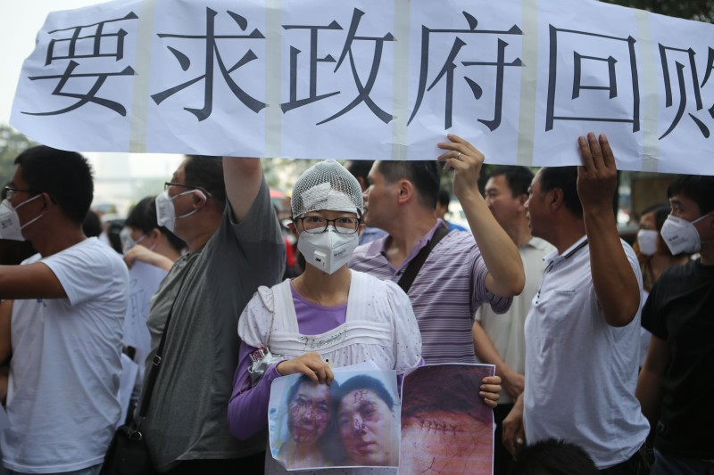 A resident injured by the explosions that hit a nearby chemical warehouse last week holds a photo of herself injured as she joins a protest outside the hotel where authorities are holding a press conferences in Tianjin on August 17, 2015. Rescuers at a Chinese industrial site where huge explosions killed at least 114 people combed through thousands of crushed shipping containers on August 17 in an effort to contain vast amounts of highly toxic cyanide, officials said, as state-run media lambasted authorities for their response to the tragedy.     CHINA OUT     AFP PHOTO        (Photo credit should read STR/AFP/Getty Images)