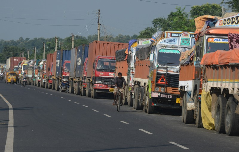 An Indian man cycles past parked Indian trucks carrying goods to Nepal near the India-Nepal border at Panitanki, some 40 kms from Siliguri on September 29, 2015. Nepal's new constitution was meant to end centuries of inequality, but instead it has sparked deadly protests and a trade blockade by ethnic minorities that has forced nationwide fuel rationing. More than 40 people have been killed in clashes between police and protesters representing ethnic minorities who say a new federal structure laid out in the constitution will leave them under-represented in the national parliament.
