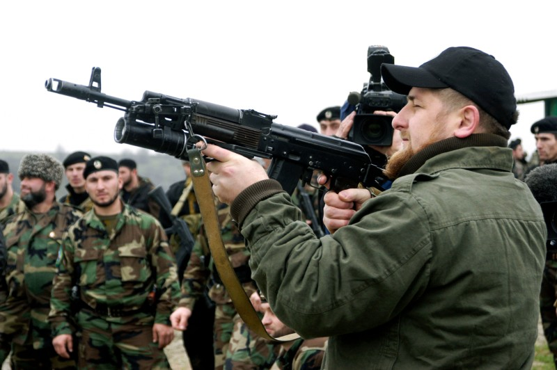 "TSENTEROI, CHECHNYA, RUSSIA - NOVEMBER 2005:  Ramzan Kadyrov proudly displays his shooting skills at a firing range in his village of Tsentoroi in front of members of his private army. Officially his army are known as the anti-terrorism squad, but everyone refers to its soldiers as Kadyrovtsy - ""Kadyrov's guys"". Ramzan was born 5 October 1976 in Tsenteroi, Chechnya, and was made Prime Minister of Chechnya in the beginning of March 2006 and leader of a powerful Chechen militia known as kadyrovtsy. He is the son of former Chechen President Akhmad Kadyrov, who was assassinated in May 2004. He has the backing of Russian President Vladimir Putin, and was awarded the Hero of Russia medal, the highest honorary title of the Russian Federation. As the head of the Chechen Presidential Security Service, Kadyrov has often been accused of being brutal, ruthless and antidemocratic; according to media and human rights groups, he was personally implicated in several instances of torture and murder. It is also rumoured that he owns a private prison in his stronghold village of Tsenteroi, where he uses inmates as a punching bags. Kadyrov is known for keeping a pet lion cub, given to him as a gift after the birth of his first son, as well as a tiger and a number of a fighting dogs, and also used to own a wolf and a bear. He has only a few classes of elementary education finished; despite his lack of education, Kadyrov is a honorary member of the Russian Academy of Sciences.  (Photo by Kadyrov Press Office/Getty Images)"