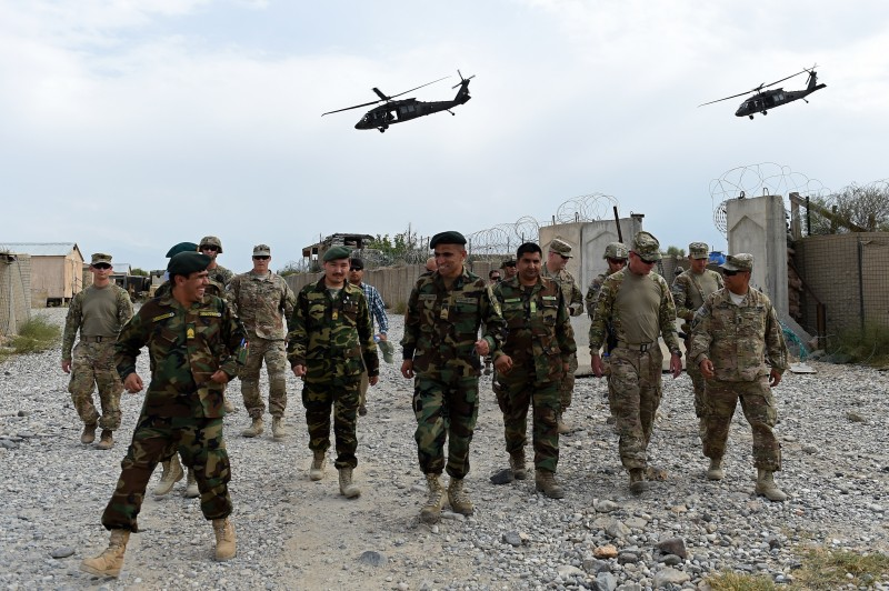 "TO GO WITH AFGHANISTAN-US-ARMY-CONFLICT-FOCUS BY GUILLAUME DECAMME In this photograph taken on August 13, 2015, US army and Afghan National Army (ANA) soldiers walk as a NATO helicopter flies overhead at coalition force Forward Operating Base (FOB) Connelly in the Khogyani district in the eastern province of Nangarhar. From his watchtower in insurgency-wracked eastern Afghanistan, US army Specialist Josh Whitten doesn't have much to say about his Afghan colleagues. ""They don't come up here anymore, because they used to mess around with our stuff. ""Welcome to Forward Operating Base Connelly, where US troops are providing training and tactical advice to the 201st Afghan army corps as they take on the Taliban on the battlefield. AFP PHOTO / Wakil Kohsar        (Photo credit should read WAKIL KOHSAR/AFP/Getty Images)"
