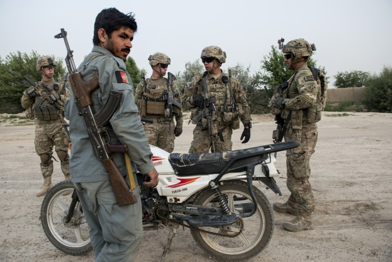 US soldiers and an Afghan police officer take a break whilst on patrol near Kandahar Airfield on June 3, 2014.  Members of the 1st Battalion, 12th Regiment, 4th Brigade Combat Team, 4th Infantry Division patrolled areas near Kandahar Airfield to protect the base from rocket attacks, and also visited Afghan police and polling stations to check on the security for the upcoming presidential election runoff.  AFP PHOTO/Brendan SMIALOWSKI        (Photo credit should read BRENDAN SMIALOWSKI/AFP/Getty Images)