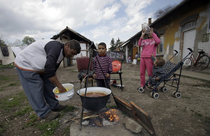 TO GO WITH AFP STORY by GREGOIRE OZAN - FILES -  A picture taken on April 22, 2012 shows a man preparing lunch with his children at their home in Miskolc. In Hungary, the proportion of children malnourished is about 14 percent, according to the latest figures published by the National Institute of Child Health.   AFP PHOTO / PETER KOHALMI        (Photo credit should read PETER KOHALMI/AFP/Getty Images)