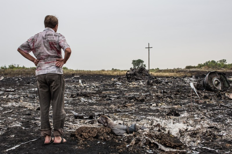 Grabovka, UKRAINE - JULY 18: A man looks at debris from an Air Malaysia plane crash on July 18, 2014 in Grabovka, Ukraine. Air Malaysia flight MH17 travelling from Amsterdam to Kuala Lumpur has crashed on the Ukraine/Russia border near the town of Shaktersk. The Boeing 777 was carrying 280 passengers and 15 crew members. (Photo by Brendan Hoffman/Getty Images) *** Local Caption ***