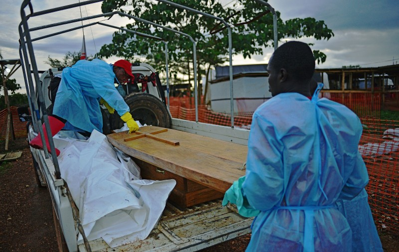 Sierra Leonese government burial team members close the lid of a coffin over the body of Dr Modupeh Cole, Sierra Leone's second senior physician to die of Ebola, on a truck at the MSF facility in Kailahun, on August 14, 2014. Kailahun along with the Kenema district is at the epicentre of the worst epidemic of Ebola since its discovery four decades ago. The death toll stands at more than 1,000. The Ebola epidemic in West Africa claimed a fourth victim in Nigeria on August 14 while the United States ordered the evacuation of diplomats' families from Sierra Leone and analysts warned of a heavy economic toll on the stricken region.   AFP PHOTO / CARL DE SOUZA        (Photo credit should read CARL DE SOUZA/AFP/Getty Images)