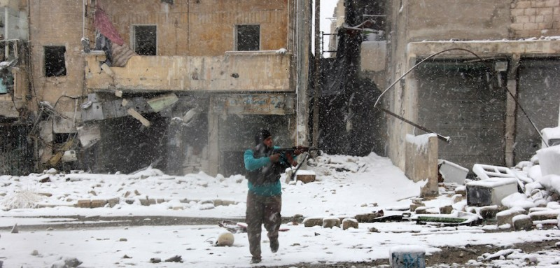 "A rebel fighter aims his weapon as he stands amidst snow during clashes with Syrian pro-government forces in the Salaheddin neighbourhood of Syria's northern city of Aleppo on December 11, 2013.  Gulf Arab states called for the withdrawal of ""all foreign forces"" from Syria, where Iran-backed Shiite militias from Iraq and Lebanon are supporting regime troops against mostly-Sunni rebels. AFP PHOTO/ZAKARIYA AL-KAFI        (Photo credit should read ZAKARIYA AL-KAFI/AFP/Getty Images)"
