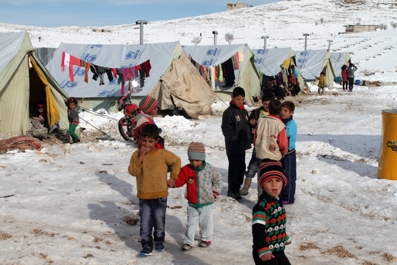 Syrian children stand in the snow in a refugee camp in the town of Arsal in the Lebanese Bekaa valley on December 13, 2013. Thousands of Syrian refugees living in makeshift camps in Lebanon were weathered a winter storm that brought snow, rain and freezing temperatures to the country. AFP PHOTO/STR        (Photo credit should read -/AFP/Getty Images)