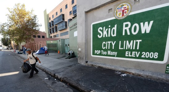"""== With AFP Story by Veronique DUPONT: US-CALIFORNIA-POVERTY-HOMELESS == A sign reading """"Skid Row"""" is painted on a wall next to the Los Angeles Mission, September 22, 2014 in Los Angeles, California. Los Angeles' Skid Row contains one of the largest populations of homeless people in the United States. AFP PHOTO / Robyn Beck (Photo credit should read ROBYN BECK/AFP/Getty Images)"""