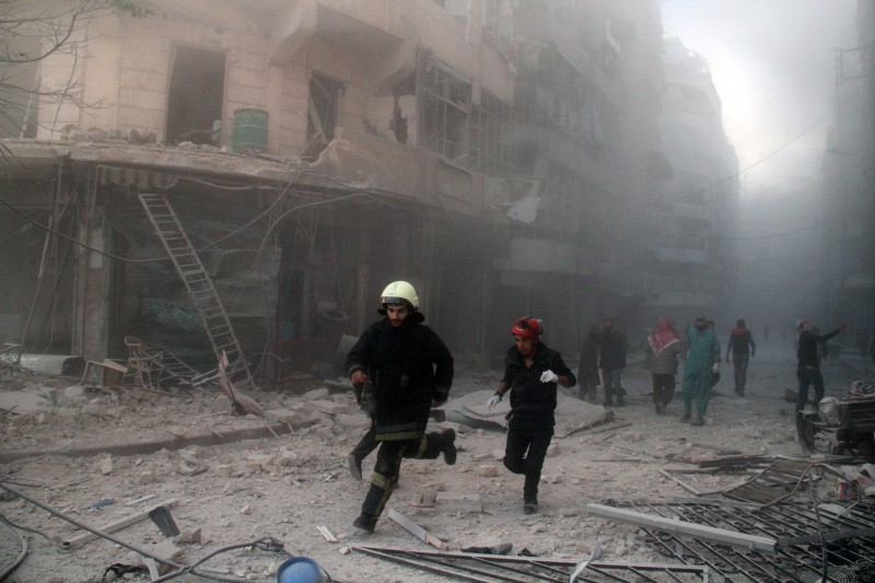 Emergency responders rush following a reported barrel bomb attack by government forces in the Al-Muasalat area in the northern Syrian city of Aleppo on November 6, 2014. Syria has asked Russia to speed up delivery of S-300 anti-aircraft missiles, concerned about a possible US attack, Syrian Foreign Minister Walid Muallem said in an interview published Thursday. AFP PHOTO/AMC/TAMER AL-HALABI        (Photo credit should read TAMER AL-HALABI/AFP/Getty Images)