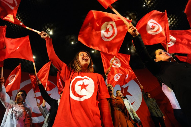Tunisians wave their national flag and shout slogans as they attend a rally marking the third anniversary of the uprising that ousted long-time dictator Zine El Abidine Ben Ali on January 14, 2014 in Habib Bourguiba Avenue in Tunis. Tunisia celebrated the third anniversary of the overthrow of a decades-old dictatorship in the first Arab Spring uprising, but political divisions have hampered the adoption of a new constitution by this symbolic deadline. AFP PHOTO / FETHI BELAID        (Photo credit should read FETHI BELAID/AFP/Getty Images)