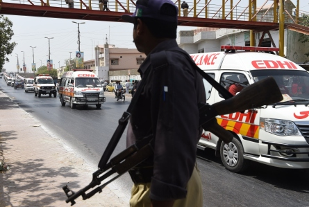 A Pakistani policeman stands guard as ambulances transport the coffins of the victims of an attack on Shiite Ismaili minority community members to a graveyard for their burial in Karachi on May 14, 2014. Pistol-wielding gunmen in Pakistan's biggest city Karachi stormed a bus carrying members of the Shiite Ismaili minority on May 13, killing at least 43 in the first attack in the country officially claimed by the Islamic State group. AFP PHOTO/ Asif HASSAN (Photo credit should read ASIF HASSAN/AFP/Getty Images)