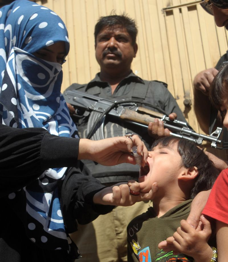 A Pakistan policeman stands guard as a member of a polio vaccination team administers drops to a child during a door-to-door vaccination campaign in Karachi on February 23, 2014. Pakistan is one of only three countries in the world where the crippling virus is still endemic, along with Afghanistan and Nigeria.   AFP PHOTO/Rizwan TABASSUM        (Photo credit should read RIZWAN TABASSUM/AFP/Getty Images)