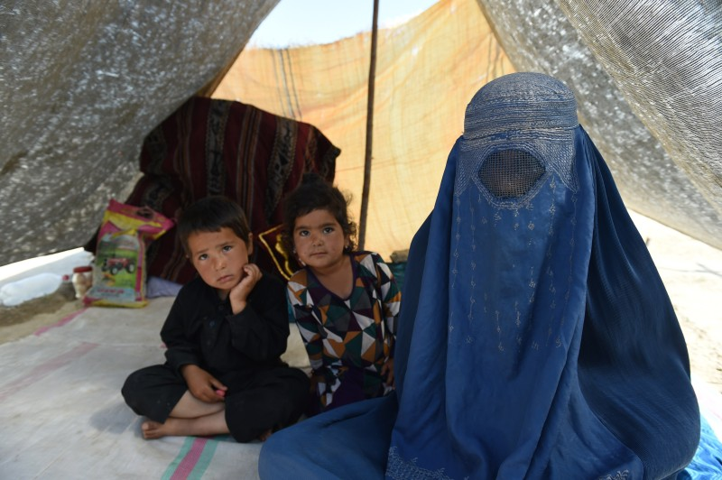 To go with Afghanistan unrest Taliban refugees,FOCUS by Anuj Chopra In this photograph taken on May 21, 2015, an Afghan woman with her children displaced by ongoing fighting against Taliban militants sit inside a tent at a makeshift camp in Kunduz, north of Kabul. Civilians are bearing the brunt of a large-scale insurgent offensive in Kunduz province, the keystone of the Taliban's summer fighting season which is expected to be the bloodiest in a decade.   AFP PHOTO / SHAH Marai        (Photo credit should read SHAH MARAI/AFP/Getty Images)