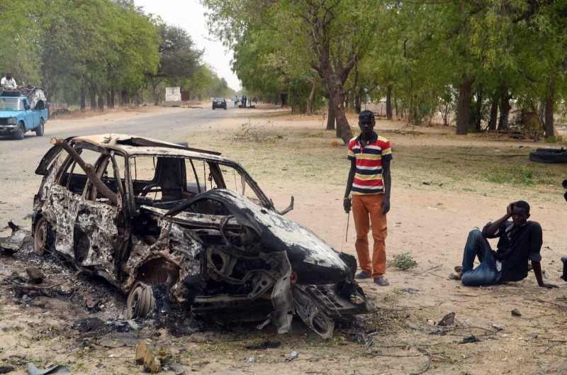 People stand by the wreckage of a car that has been blown up by suspected Boko Haram militants in Nigeria's troubled northeastern city of Maiduguri on March 25, 2014, killing five police officers, while a separate blast killed three. The attacks were the latest to hit the Borno state capital, which is the epicentre of Boko Haram's brutal insurgency which has killed thousands since 2009, including more than 700 this year.  AFP PHOTO        (Photo credit should read -/AFP/Getty Images)