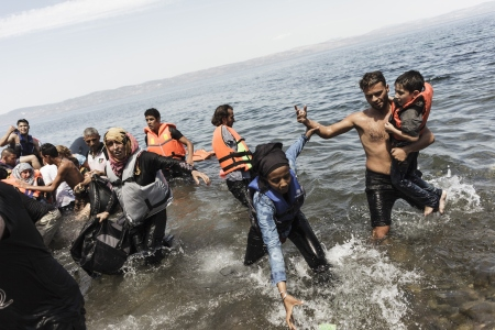 """A woman reaches out for a document she dropped in the water as migrants get off of an inflatable boat after arriving on the Greek island of Lesbos after crossing the Aegean sea from Turkey to Greece on August 14, 2015. Turkish efforts to stop traffickers from sending large """"ghost ships"""" crammed with migrants towards Italy has sparked the surge in arrivals in Greece, the International Organization for Migration said on August 13. The migrants and refugees making the perilous journey across the Mediterranean to Europe are increasingly travelling the eastern route from Turkey to the Greek islands, which have seen more arrivals since the beginning of the year than long-time top destination Italy, according to UN figures. AFP PHOTO / ACHILLEAS ZAVALLIS (Photo credit should read ACHILLEAS ZAVALLIS/AFP/Getty Images)"""
