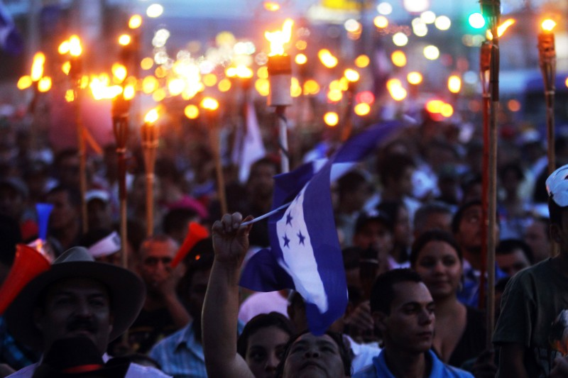 """Demonstrators demanding the resignation of President Juan Orlando Hernandez over an ongoing corruption scandal demonstrate in Tegucigalpa on August 28, 2015. The demonstrators, known as """"indignados"""" -- the indignant ones -- march with torches demanding the creation of an anti-corruption commission and calling for Hernandez to go while rejecting any dialogue with him. AFP PHOTO/ STR        (Photo credit should read STR/AFP/Getty Images)"""