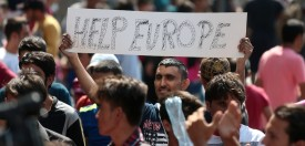 "A man hold a placard reading ""Help Europe"" as Syrian and Afgan refugees attend a protest rally to demand to travel to Germany on September 2, 2015 outside the Keleti (East) railway station in Budapest. Hungarian authorities face mounting anger from thousands of migrants who are unable to board trains to western European countries after the main Budapest station was closed.  AFP PHOTO / FERENC ISZA        (Photo credit should read FERENC ISZA/AFP/Getty Images)"