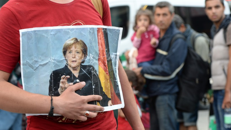 A refugee holds a picture of German Chancellor Angela Merkel after the arrival of refugees at the main train station in Munich, southern Germany, September 05, 2015. Hundreds of refugees arrived in Germany on September 5, 2015 coming from Hungary and Austria. AFP PHOTO / CHRISTOF STACHE        (Photo credit should read CHRISTOF STACHE/AFP/Getty Images)